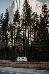 Camper moving on street with trees and mountain in background