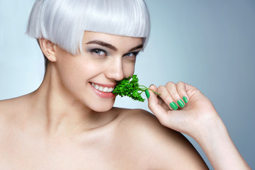Beautiful smiling girl with parsley. Photo of fashion blonde girl on blue background. Close up. Healthy lifestyle concept