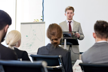 Portrait of young businessman standing by podium while giving speech at conference before audience, copy space