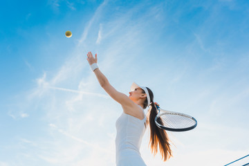 Woman playing tennis giving service throwing ball in the air