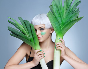 Pretty girl with green leeks. Photo of smiling blonde girl on blue background. Detox concept