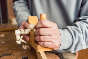 Hand of a senior carpenter with wood planer, closeup