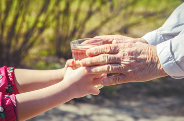 Grandmother giving a glass of clean water to a child. Selective focus.