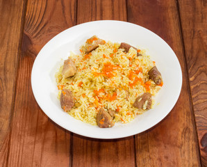Cooked pilaf on dish on wooden surface