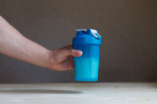 Hand holding plastic shaker with protein shake and glass on table. Man's fist holding the post workout chocolate whey protein shake, ready to drink it, isolated on wooden background