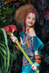 A beautiful little girl with flower wearing native costume in the jungle or rainforest.