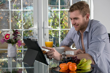 Handsome young man sitting at breakfast table with orange juice, cereal, coffee and fruit, using digital tablet , device