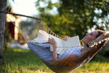 Beautiful young girl lying and reading a book