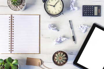 Top view on a white desk with an open notebook, tablet, clock, plants and crumpled sheets of paper