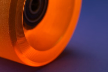A macro of a longboard roll in orange on blue underground