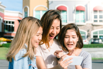 Group of young Asian Women selfie themselves with a phone in a pastel town after shopping. Young women group do outdoor activity under the blue sky. Outdoor activity after shopping concept.