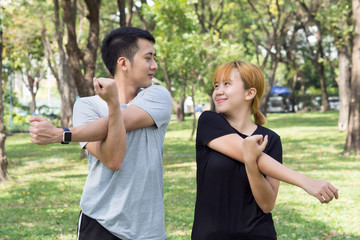 Asian sweet couple warm up their bodies by stretching arms before morning jogging exercise in the park surrounded with nature and warm light sunshine. lover couple exercise together outdoor with love.