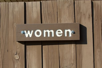 A wood women sign on the door and a close up view.