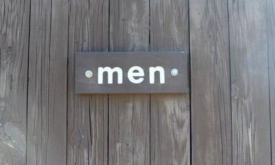 The men wood sign on the door and a close up view.