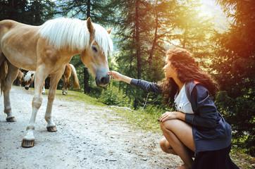 Hübsche junge Frau mit lockigem Haar in der Hocke streichelt ein Pferd im Wald