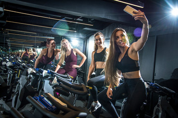 Sporty girls taking selfie while sitting on exercise bikes in gym