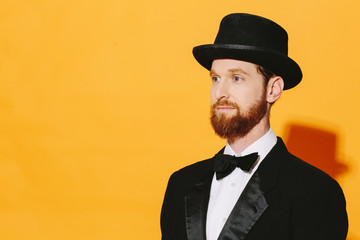 Portrait of a man with red beard in top hat and bow tie looking to side, isolated on yellow studio  background