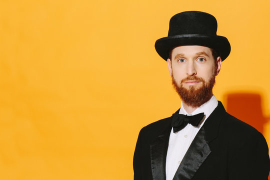Portrait of a man with red beard in top hat and bow tie looking at camera, isolated on yellow studio  background
