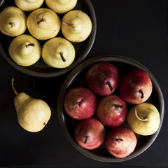 Several yellow and red pears in bowls