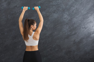 Fitness model woman with dumbbells on grey background