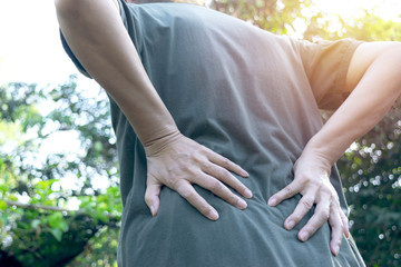 Women's back pain outdoor while at work.