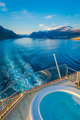 Above outdoor view of Hurtigruten voyage in cruise along Norwegian coast with a luxury swimming pool with a gorgeous nature background
