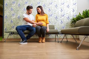 A beautiful young pregnant couple sitting in the doctors waiting room.
