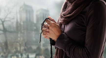 Foto En Lienzo - Woman praying with rosary and wooden cross in hand on church background. Hope concept