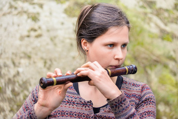 Woman playing an indian wooden flute
