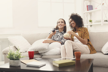 Smiling female friends watching TV at home