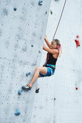 young woman climber climbs on the open climbing gym