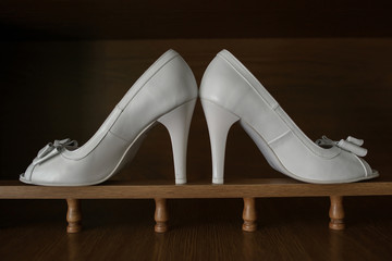 White leather high heels shoes in pair, with stylish bow against dark brown background