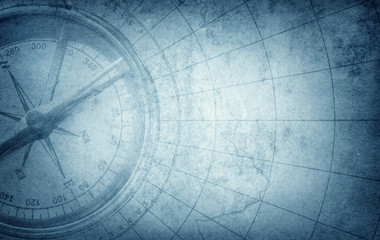 Old vintage retro compass on ancient map. Survival, exploration and nautical theme grunge blue background