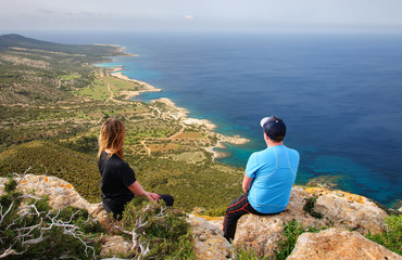 Photo sur Aluminium Chypre man and woman sitting on rock and looking at the Mediterranean Sea