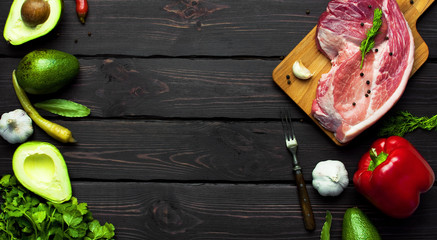 Raw meat with herbs, fresh vegetables, avocado, pepper, coriander, dill, garlic, chili and spices on a dark wooden background. Raw steak from pork or beef. Cooking concept. Top view. Copy space