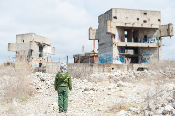little child in jacket stands against ruins of building as result of war conflict