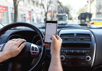 Man sending message from a smartphone while driving a car can cause accident or its dangerous