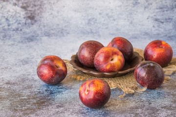 Fresh large ripe plums in a small round vase on a napkin from a burlap on a blue background.