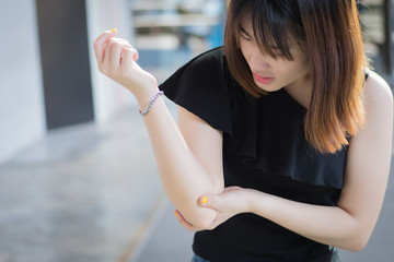 injured woman with elbow joint bone injury; portrait of  sick injured woman suffering from elbow joint pain injury, rheumatoid or gout arthritis health care concept; young adult asian woman model
