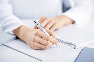 Closeup photo of businesswoman's hand holding pen and writing something while using mobile phone