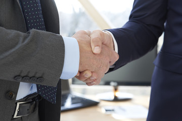 Handshake. Close-up shot of two businessman wearing suit and shaking hands.