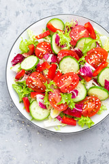Fresh vegetable salad with tomatoes, cucumbers, sweet pepper and sesame seeds. Vegetable salad on white plate