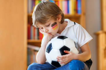 Sad and not happy little kid with football about lost football or soccer game. child after watching match on tv