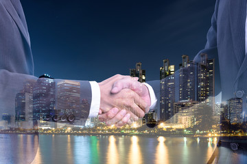 Concept business :  Double exposure of businessman making handshake with background of night city
