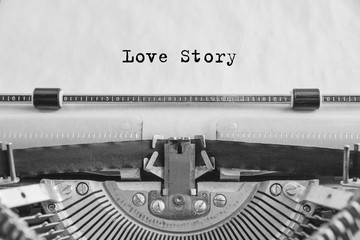 love story text is typed on an old vintage typewriter with white paper. love sign
