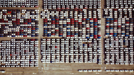 Aerial view of a parking lot new cars lined up in the port for import and export.