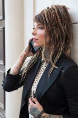 Tattooed businesswoman with dreadlocks talking on phone