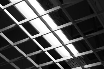 Dark ceiling office light with plastic square grid in the shopping centre