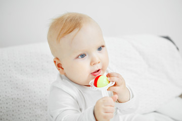 Cheerful baby sits on bed and holds rattle