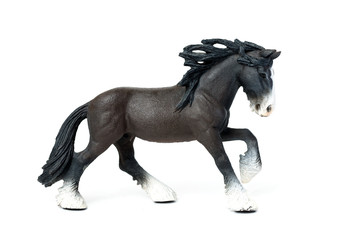 Figurine of a black horse jumps, on a white background.